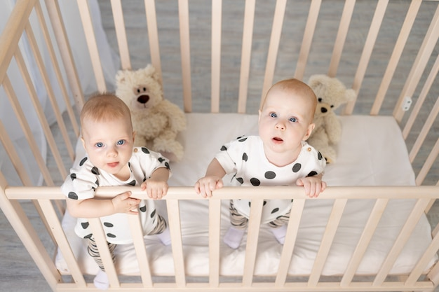 Zwei baby zwillinge bruder und schwester 8 monate sitzen in ihrem pyjama in der krippe und schauen in die kamera, draufsicht, das konzept der freundschaft, ein ort für text