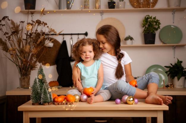 Zwei babys, die mandarinen in der weihnachtsküche essen