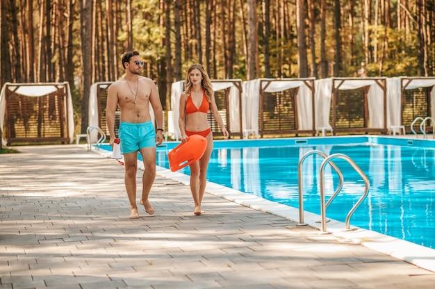 Zwei bademeister laufen in der nähe des öffentlichen schwimmbads und unterhalten sich