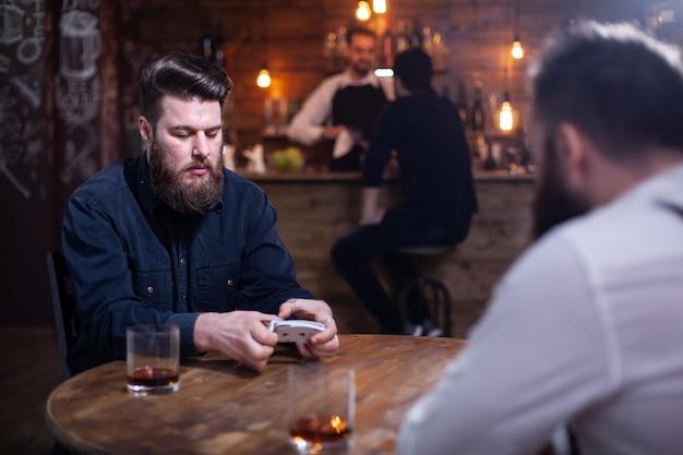 Zwei bärtige hipster, die in einem vintage-pub ein kartenspiel spielen. ein barkeeper mit einem kunden ist im hintergrund