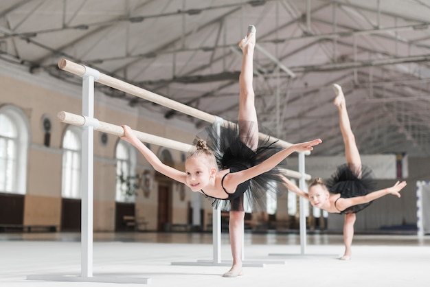 Zwei ballerinamädchen, die oben ihre beine mit barreresupport in der tanzklasse ausdehnen