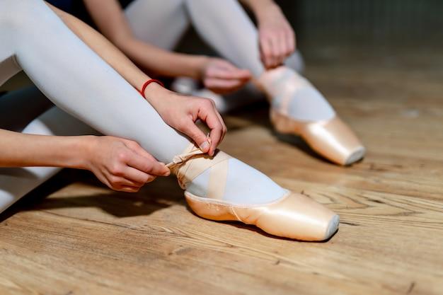 Zwei ballettmädchen, die auf ihre spitzenschuhe sitzen auf dem bretterboden sich setzen. balletttänzer, die ballettschuhe binden. nahansicht