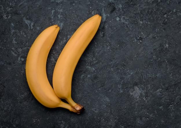 Zwei bananen auf einem schwarzen betontisch. tropische früchte. trend des minimalismus. draufsicht.