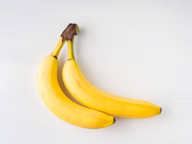 Zwei bananen auf weißem hintergrund. minimale flachlage