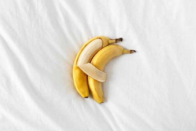 Zwei bananen liegen nebeneinander und umarmen sich wie menschen.