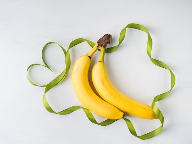 Zwei bananen mit grünem bandrahmen und herzsymbol auf weiß