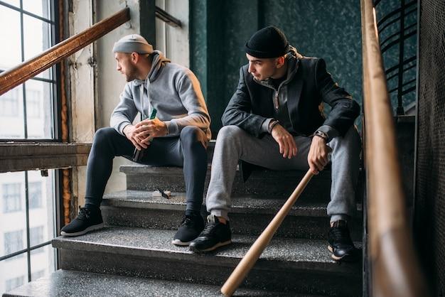 Zwei banditen mit baseballschläger warten auf opfer