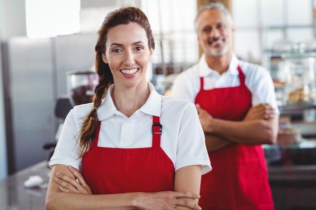 Zwei baristas, die an der kamera mit den armen gekreuzt lächeln