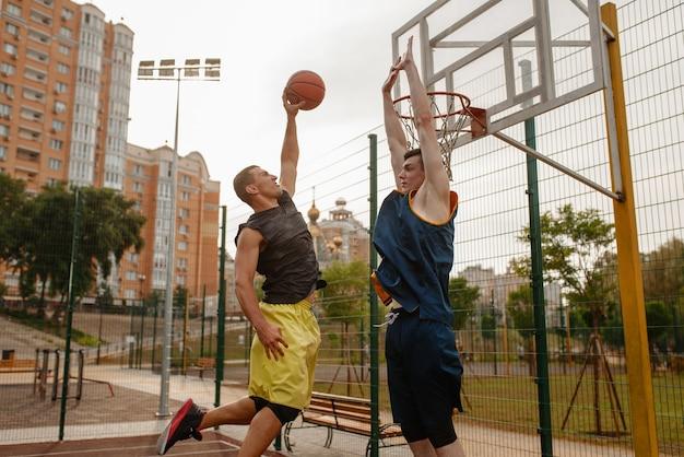 Zwei basketballspieler, die auf dem außenplatz spielen.