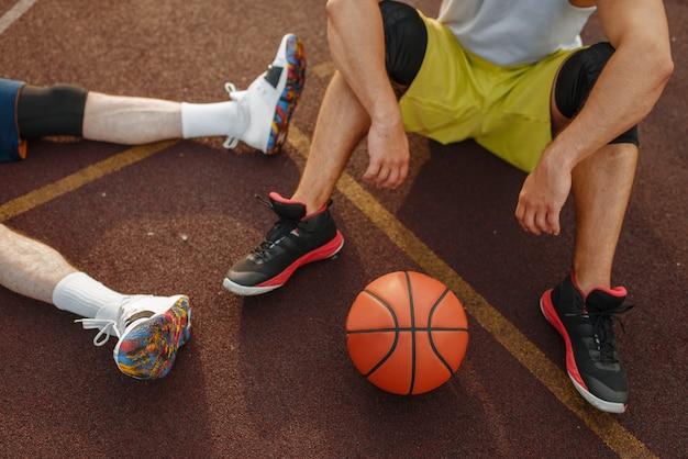 Zwei basketballspieler, die auf dem boden auf dem außenplatz sitzen.