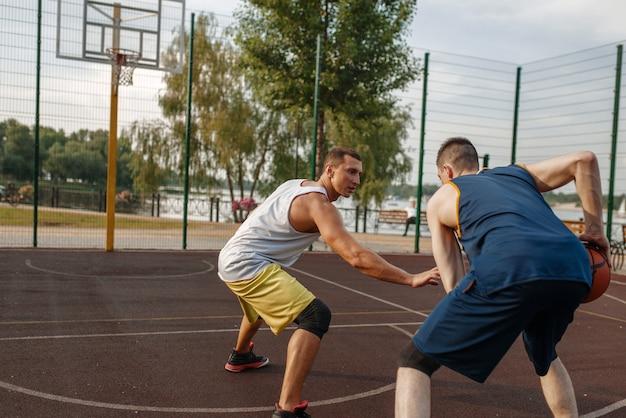 Zwei basketballspieler, die intensives spiel auf dem außenplatz spielen.