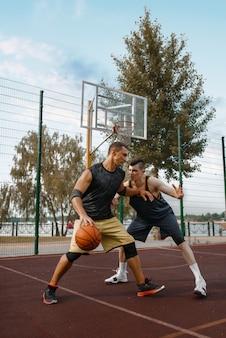 Zwei basketballspieler veranstalten ein spiel auf dem platz im freien, aktive freizeit.