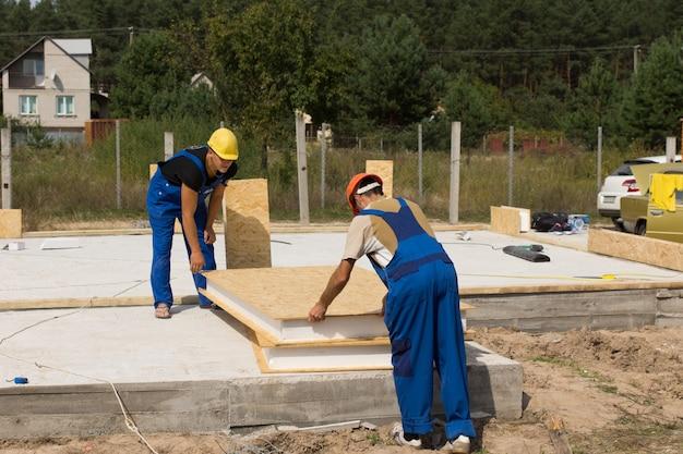Zwei bauarbeiter oder bauarbeiter, die isolierte wandpaneele handhaben, während sie sich darauf vorbereiten, sie auf dem boden und dem fundament eines neu gebauten hauses zu installieren