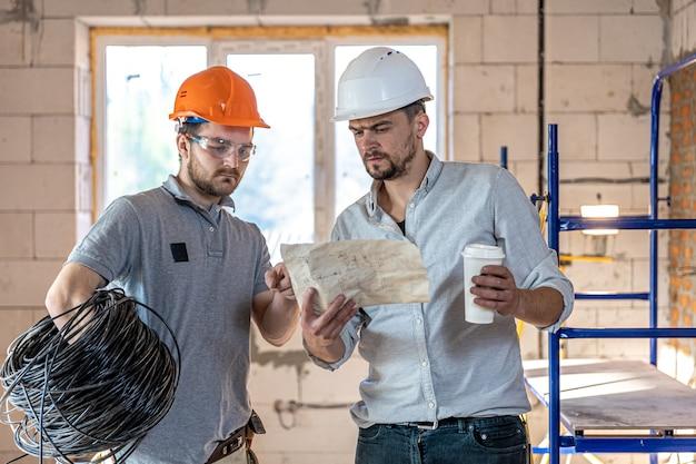 Zwei bauingenieure sprechen auf der baustelle, ingenieur, der einem arbeiter eine zeichnung erklärt.