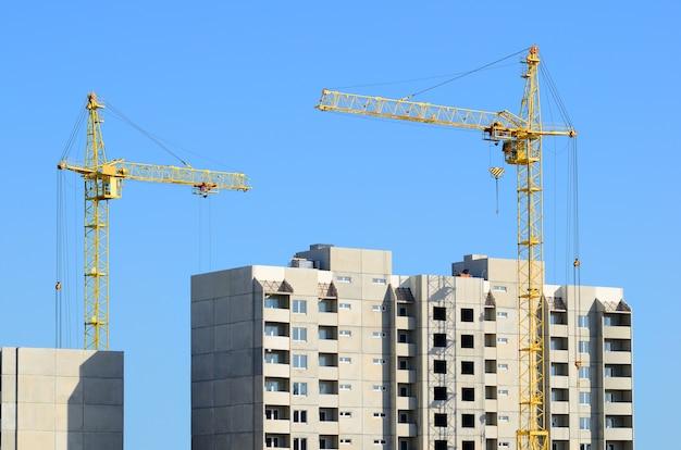 Zwei baukräne und betongebäude auf blauem himmel