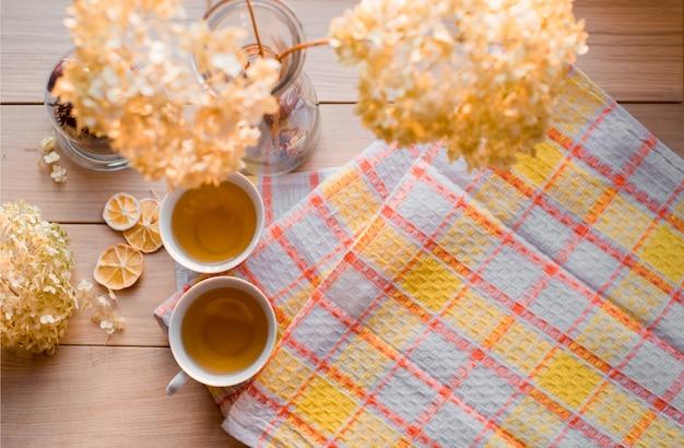 Zwei becher heißer tee auf einer gelben leinenserviette