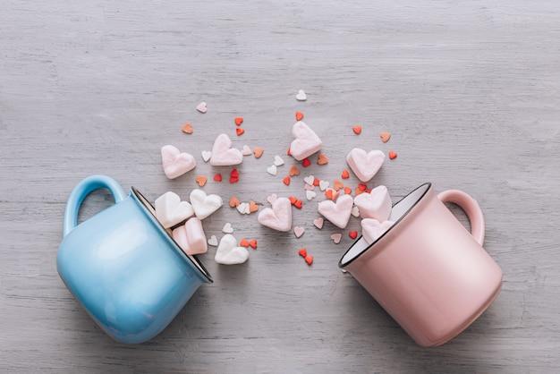 Zwei becher mit blau und rosa liegen auf der seite, kleine süßigkeitenherzen und marshmallowherzen sind herausgelaufen