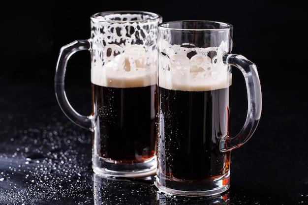 Zwei becher schaumiges bier auf schwarzem hintergrund
