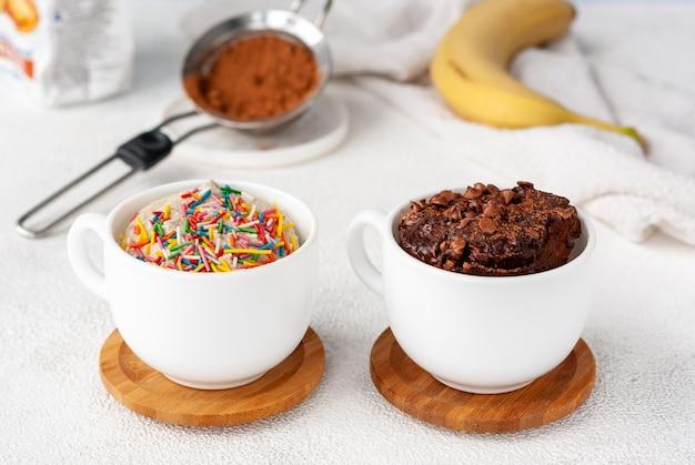 Zwei becherkuchen, hell und dunkel, stehen zusammen auf einem tisch