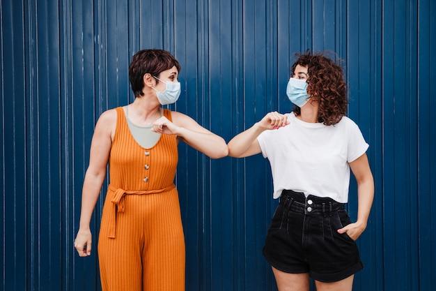 Zwei befreundete frauen im freien tragen gesichtsmaske, grüßen mit ellbogen und schauen sich an. pandemie während des corona-virus. konzept der sozialen distanz