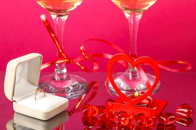 Zwei beine von champagnergläsern gebunden mit roten bändern auf einem rosa hintergrund neben einem ring in einer schachtel eine kerze in einem herzleuchter. horizontales foto