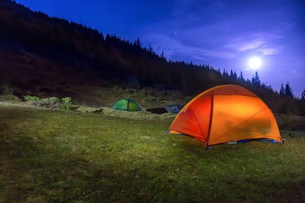 Zwei beleuchtete orange und grüne campingzelte unter mond, sterne in der nacht