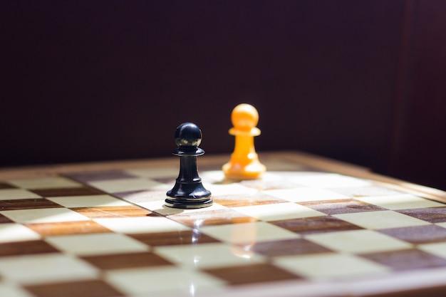 Zwei beleuchtete schachfiguren auf dem spielbrett covid-trennungsabstandssymbol