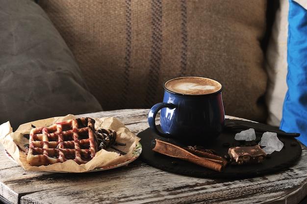 Zwei belgische waffeln mit himbeermarmelade und schokolade und cappuccino