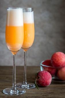 Zwei bellini-cocktails mit frischen pfirsichen