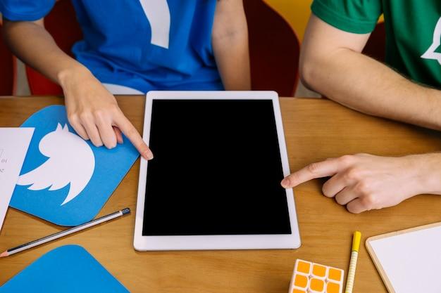 Zwei benutzer, die auf digitale tablette mit leerem bildschirm zeigen