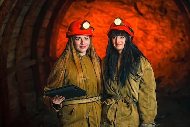 Zwei bergleute in der mine. mädchen in roten helmen und laternen in einer kohlengrube.