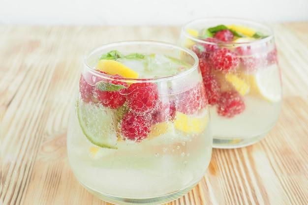 Zwei beschlagene gläser mit eislimonade und früchten und beeren, zitrone, limette und minze in soda-blasen. sommerkühlgetränk.