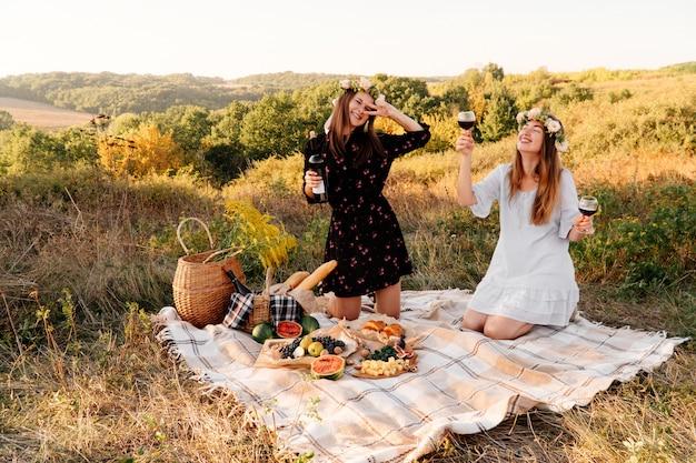 Zwei beste freunde auf picknick auf dem gebiet, das auf das gelegte lächeln legt