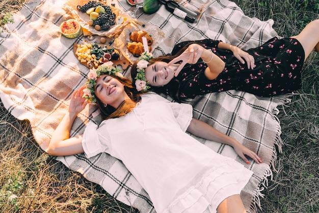 Zwei beste freunde auf picknick im feld, das auf die gelegte lächelnde draufsichtfreundschaft legt
