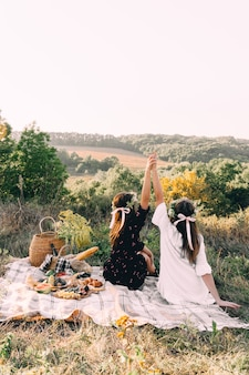 Zwei beste freunde auf picknick im feldhändchenhalten im freiheitskonzept