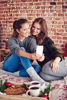 Zwei beste freunde, die selfie im schlafzimmer nehmen
