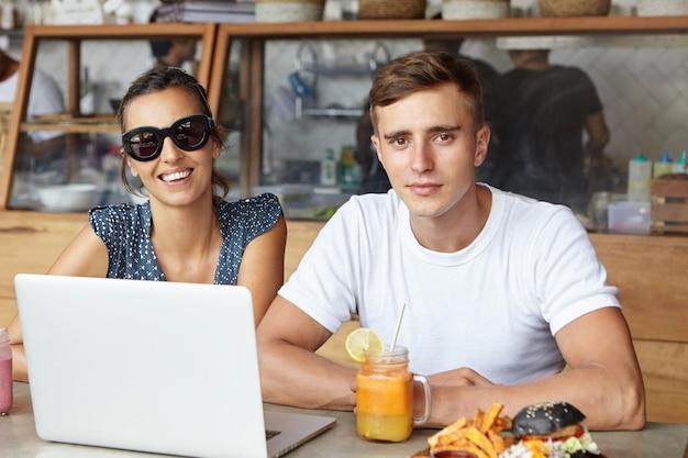 Zwei beste freunde, die während des mittagessens einen laptop benutzen, in einem gemütlichen café sitzen und mit einem glücklichen lächeln schauen. studenten, die online auf einem notebook-pc lernen