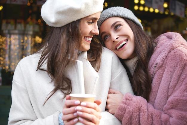 Zwei beste freunde, die zeit auf dem weihnachtsmarkt genießen