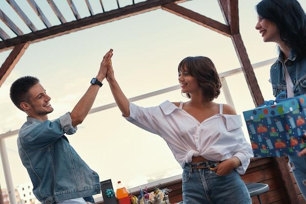 Zwei beste freunde geben sich fünf und lächeln, während sie auf dem dach stehen