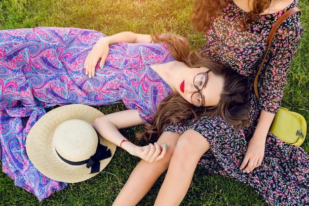 Zwei beste freunde in buntem boho-kleid und lockigem haar, die auf dem grünen gras liegen