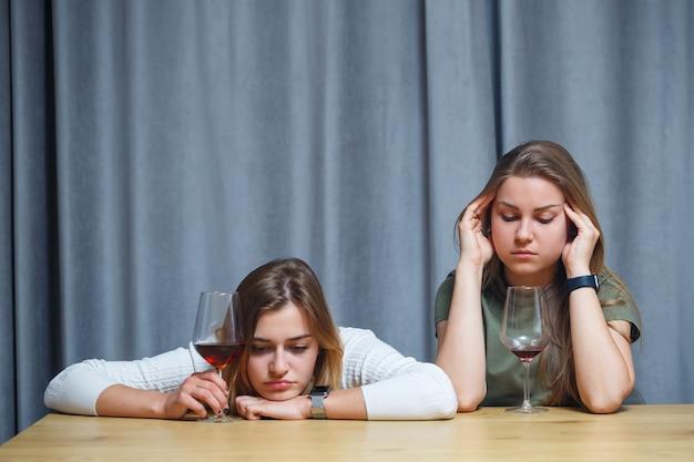 Zwei beste freunde. junge europäisch aussehende frauen unterhalten sich mit einem glas wein an einem schreibtisch. schöne mädchen schwestern trinken gerne alkohol lachen fröhlich entspannen im wohnzimmer