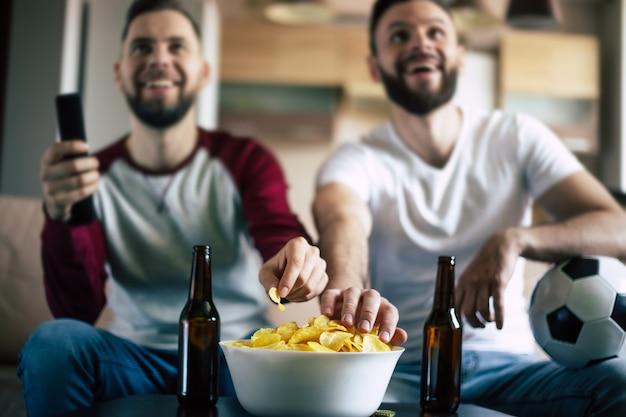 Zwei beste freunde und fußballfans schauen sich ein sportspiel im fernsehen an, trinken bier und essen snacks, während sie das team auf der couch anfeuern