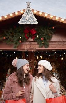Zwei beste freundinnen auf dem weihnachtsmarkt