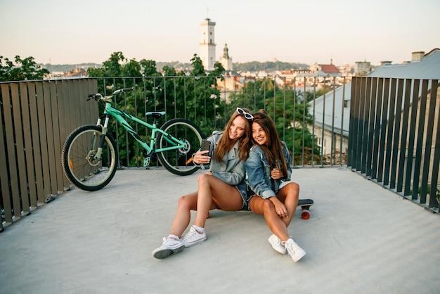 Zwei beste freundinnen, die selfie mit smartphone nehmen, wenn sie auf skateboarding sitzen, während sie am sonnigen sommertag gehen. draußen. zeitlupe