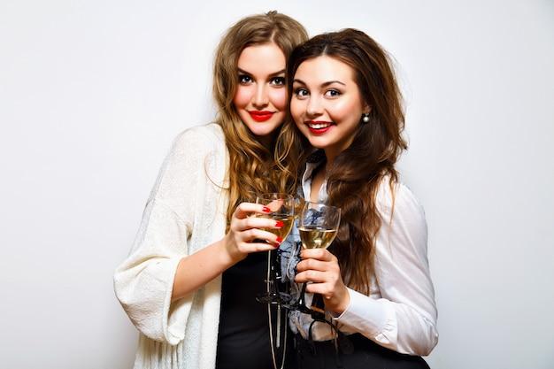 Zwei beste freundinnen, die spaß auf schwarzweiss-partei haben, trinken champagner lächelnd und klatsch, freudige schwestern, die geburtstagsfeier feiern, elegante stilvolle kleidung, weißer hintergrund.