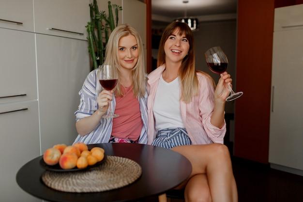Zwei beste freundinnen, die wein auf küche genießen. gemütliche häusliche atmosphäre. teller mit frischen früchten.