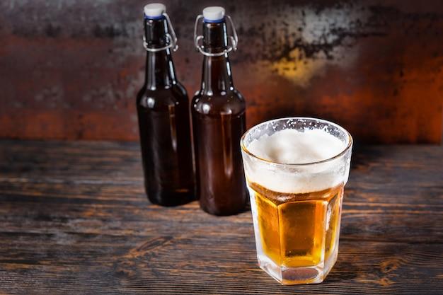 Zwei bierflaschen in der nähe von glas mit einem hellen bier und einem schaumkopf auf einem alten dunklen schreibtisch. getränke- und getränkekonzept
