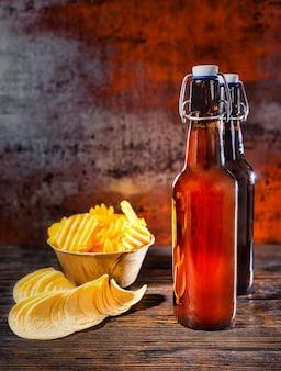 Zwei bierflaschen in der nähe von verstreuten pommes und einem teller mit snacks auf einem dunklen holzschreibtisch. lebensmittel- und getränkekonzept