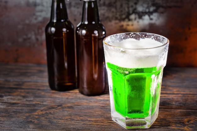 Zwei bierflaschen neben glas mit einem grünen bier und einem schaumkopf auf einem alten dunklen schreibtisch. getränke- und getränkekonzept