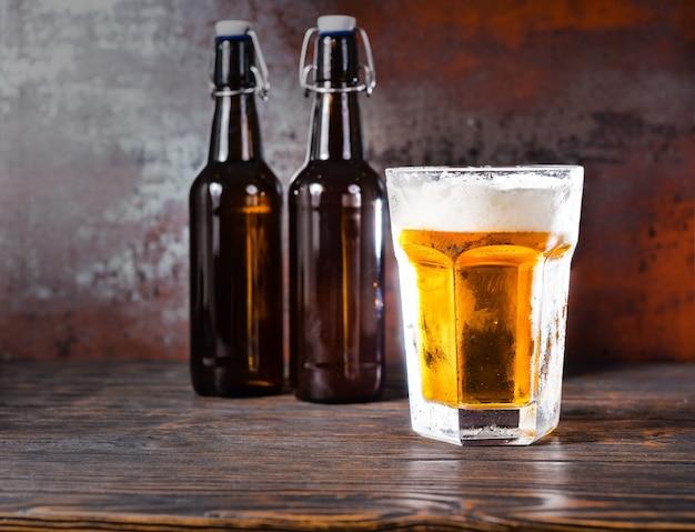 Zwei bierflaschen neben glas mit einem hellen bier und einem schaumkopf auf einem alten dunklen schreibtisch. getränke- und getränkekonzept